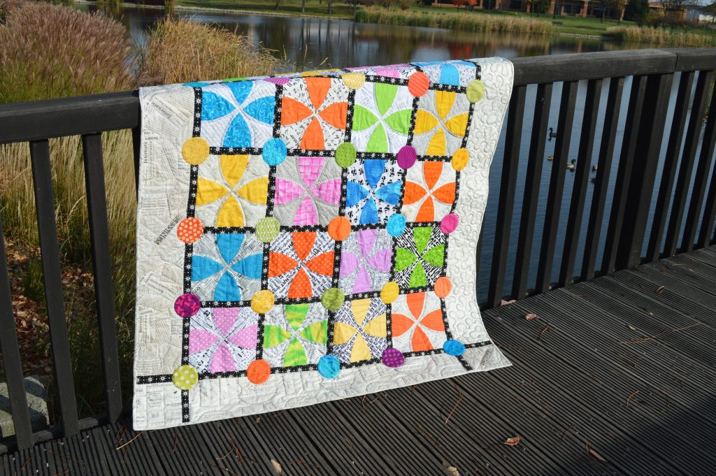 Whimsy Garden quilt pattern by Sharon McConnell Color Girl Quilts with bright colors, low volume fabrics, curved piecing